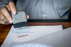 Hands of businessman stamp on paper document to approve business investment contract agreement.  stock photo