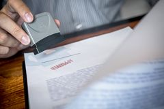 Hands of businessman stamp on paper document to approve business investment contract agreement stock photography
