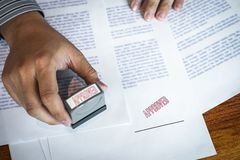 Hands of businessman stamp on paper document to approve business investment contract agreement royalty free stock images