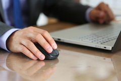 Hands of businessman in suit holding computer wireless mouse. Working with notebook pc. Working with computer, internet surfing, entertainment or business Royalty Free Stock Photography