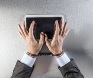 Hands of businessman using a digital tablet with slave handcuffs Stock Photo