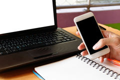 Hands of a businessman using smart phone with blank laptop scree. N Stock Photography