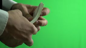 Hands of a businessman holding a bundle of one hundred dollar bills on a green screen. In the hands of a businessman in a white shirt a bunch of one hundred stock footage
