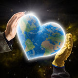 Hands of businessman and worker holding heart-shaped Earth. Hands of businessman and worker holding heart-shaped Planet Earth stock photography