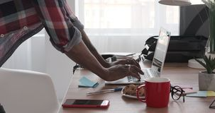 Hands of businessman working on laptop at office. Hands of african american businessman working on laptop at office desk stock video footage