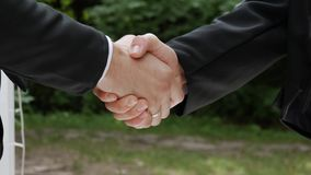Shake hands of businessmen. Hands of businessmen on the background of trees. Entrepreneur and businessman draw up a deal, shake hands stock footage