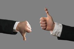Hands of businessmen with chess pieces as thumbs Stock Images