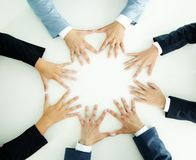 Hands of businesspeople. Top view of businesspeople holding hands together on a plain white surface Stock Images