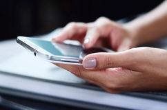 Hands of a businesswoman using a smartphone. Hands of a beautiful businesswoman using a smartphone Stock Photo