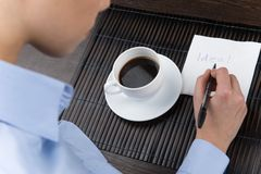 Hands of businesswoman writing on paper napkin on coffee table. Stock Photo