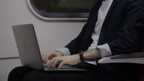 Hands of busnessman, who is writing a report on laptop in the train. Male professional is sitting on comfortable seat near the window, holding his brand-new stock footage