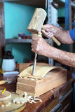 Hands of cabinetmaker carving wood with a chisel and hammer Stock Photos
