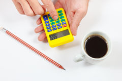 Hands calculate using a pocket calculator on white background stock image