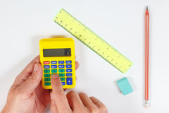 Hands calculate using a pocket digital calculator over a workplace of engineer Royalty Free Stock Photo