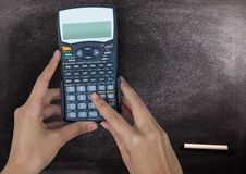 Hands with calculator against chalkboard. Digital composite of Hands with calculator against chalkboard Royalty Free Stock Images
