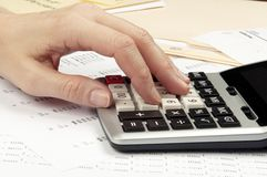 Hands on calculator with financial papers Royalty Free Stock Image