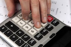 Hands on calculator with financial papers Royalty Free Stock Photo