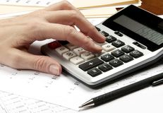 Hands on calculator  with pen and financial papers Stock Photography