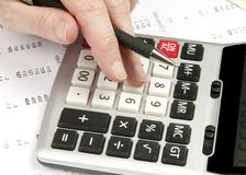 Hands on calculator  with pen and financial papers Stock Image