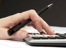 Hands on calculator  with pen and financial papers Royalty Free Stock Photography