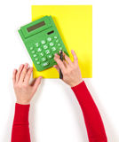 Hands with calculator and yellow sheet of paper Royalty Free Stock Images