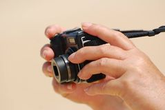 Hands with camera in focus Stock Images