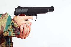 Hands in camouflage uniform with automatic army handgun Royalty Free Stock Photos
