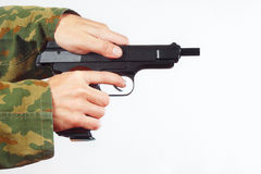 Hands in camouflage uniform reload pistol Stock Photography