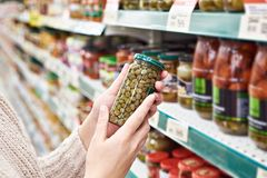 Hands with can of canned capers in store Stock Image