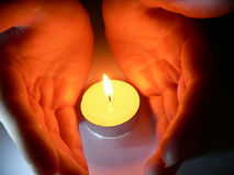 Hands and a candle Stock Photography
