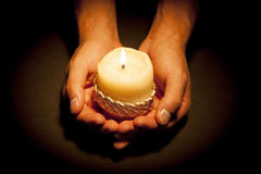 Hands with candle. Praying Hands with candle in black background Royalty Free Stock Images