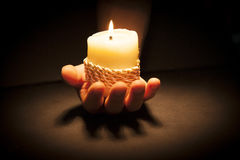 Hands with candle. Praying Hands with candle in black background Royalty Free Stock Image