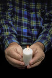 Hands and candle. View of an old man hands holding a burning candle Royalty Free Stock Photos