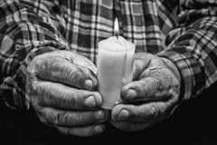 Hands and candle. View of an old man hands holding a burning candle Stock Photos