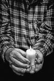 Hands and candle. View of an old man hands holding a burning candle Royalty Free Stock Image