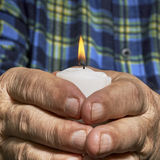Hands and candle. View of an old man hands holding a burning candle Stock Photography