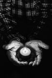 Hands and candle. View of an old man hands holding a burning candle Stock Images