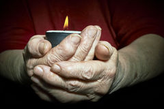 Hands and candle. View of an old woman hands holding a burning candle Royalty Free Stock Photos