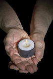 Hands and candle. View of an old woman hands holding a burning candle Stock Images
