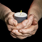 Hands and candle. View of the old woman hands holding a burning candle on a black background Royalty Free Stock Photography
