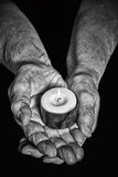 Hands and candle. View of the old woman hands holding a burning candle on a black background Stock Photos
