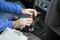 The hands of the car electrician connect the cables from the radio to the car`s electrical system. The hands of the car electrician connect the cube cords of royalty free stock photos