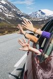 Hands of the car. Happy trip - hands of men and children peering out of the car on a background of mountains royalty free stock images