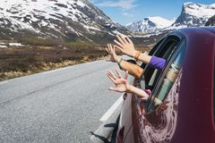 Hands of the car. Happy trip - hands of men and children peering out of the car on a background of mountains royalty free stock image