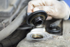 The hands of the car mechanic unscrew the cap of the oil filler. Royalty Free Stock Photos