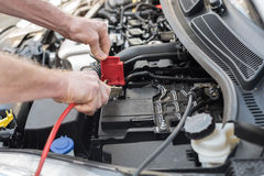 Hands of car mechanic using car battery jumper cable. Hands of car mechanic using cables to start a car engine Stock Image
