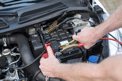 Hands of car mechanic using car battery jumper cable. Hands of car mechanic using cables to start a car engine Royalty Free Stock Images