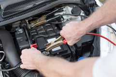 Hands of car mechanic using car battery jumper cable. Hands of car mechanic using cables to start a car engine Royalty Free Stock Photos