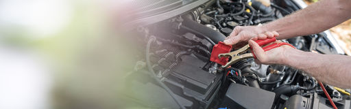Hands of car mechanic using car battery jumper cable. Hands of car mechanic using cables to start a car engine Stock Images