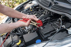 Hands of car mechanic using car battery jumper cable Stock Photos